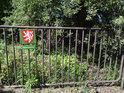 Úřední cedule na kovovém plotě.