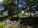 Suchá hráz mezi stromy z posbíraných plochých kamenů.