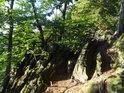 Pěšina mezi nakloněnými skalními vrásami.