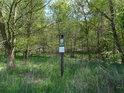 Úřední a informační cedule k chráněnému území na okraji lesa.