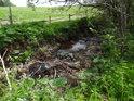 Potok s minimálním množstvím vody podél cesty u chráněného území Bedřichovka.