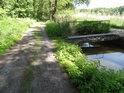 Zpevněná cesta mezi Bohdanečskými rybníky a ocelová lávka přes napájecí strouhu.