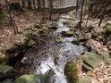 Zaječí potok se blíží k uměle zbudované kamenné hrázi.