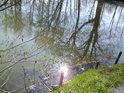 Odraz Slunce ve vodní hladině úplně pohlcuje kůl hacení.