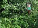 V zeleni zpola utopená úřední cedule k chráněnému území Dědina u Dobrušky.