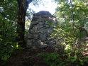 Kamenný pomník S. K. Neuman pohledem zezadu z lesa.