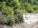 Okraj opěrné zdi nad železniční tratí.