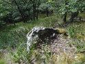Tak trochu vylámaný balvan v lesním svahu.