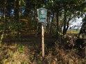 Úřední a informační cedule na kraji lesa.