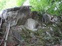Pod skalou, na níž ještě dopadá sluneční svit.