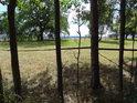 Pohled z lesa na louku přes ohradu pastviny.