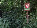 Úřední cedule pod stromy na okraji lesa.