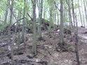 Skály se tyčí nad levým břehem levostranného přítoku říčky Hučava.