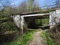 Železniční most přes potok Mlýnka se souběžnou cestou.