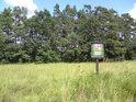 Od polí na západní straně odděluje chráněné území starší ochranná cedule.
