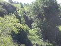 Skála nad tratí dosahuje výšky dospělého stromu.