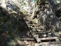 Dřevěný žebřík ve skalách doleva zalomený.