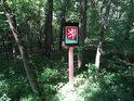 Úřední cedule v lese u cesty.