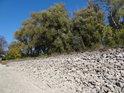 Kamenný val hráze rybníka v době vypuštění.