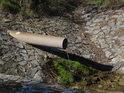 Trubkový propustek kamennou hrází rybníka zajišťuje průtok původního potoka.